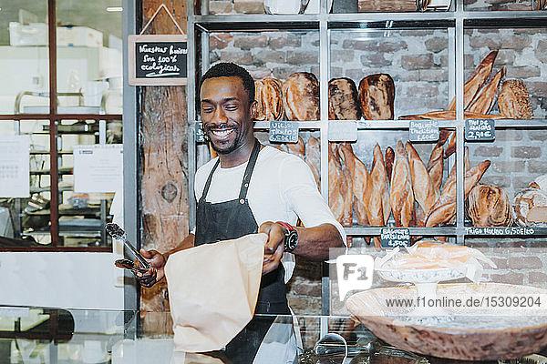 Lächelnder Mann bei der Arbeit in einer Bäckerei
