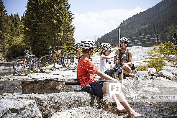 Mutter und ihre Kinder machen während einer Fahrradtour an einem Gebirgsbach Rast