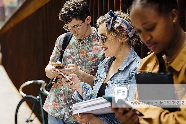 Studenten  die sich in einem Hinterhof treffen  reden  Smartphones entsorgen