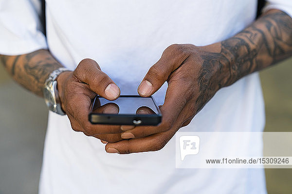 Hände eines tätowierten Mannes mit Smartphone  Nahaufnahme