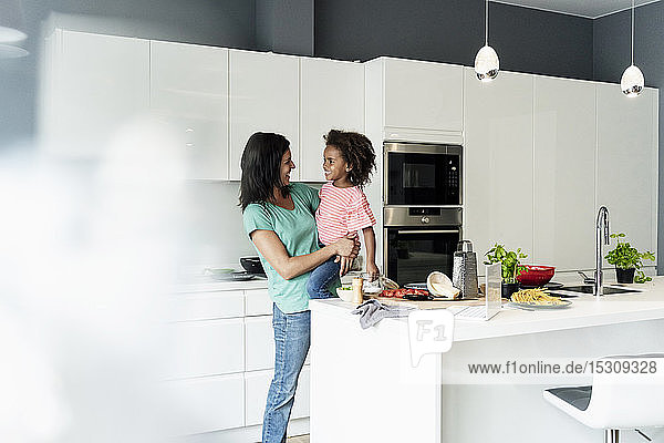 Happy mother holding daughter in kitchen