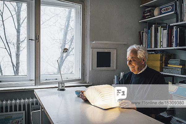 Älterer Mann mit leuchtendem Buch auf dem Tisch zu Hause