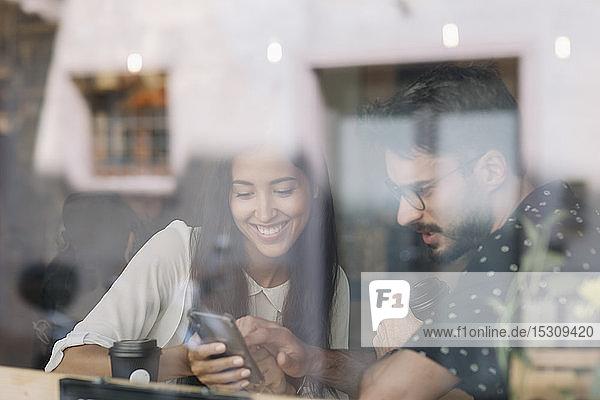 Junges Paar mit Smartphone hinter einer Fensterscheibe in einem Café