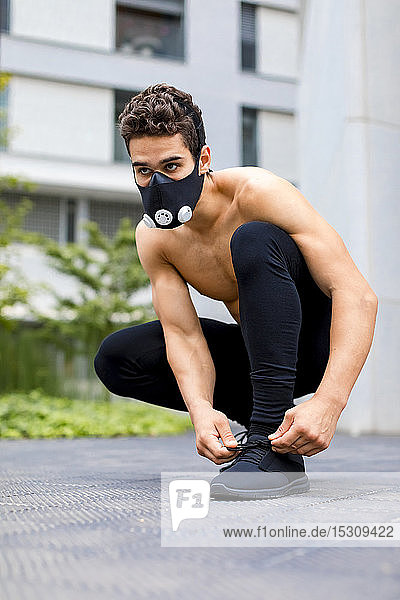 Young athlete tying shoes  wearing breathing mask