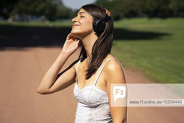 Porträt einer jungen Frau mit Kopfhörern in einem Park im Sommer
