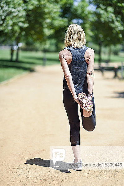 Mature woman stretching leg on a path in a park