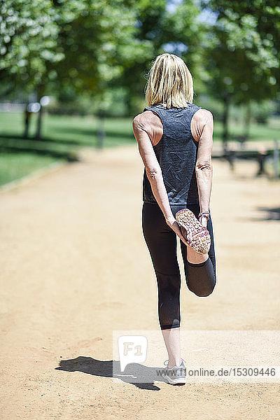 Eine reife Frau streckt ihr Bein auf einem Weg in einem Park
