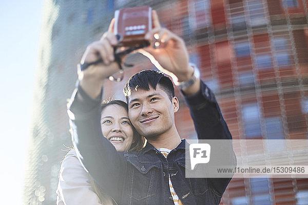 Porträt eines sprechenden Paares mit Sofortbildkamera  Barcelona  Spanien