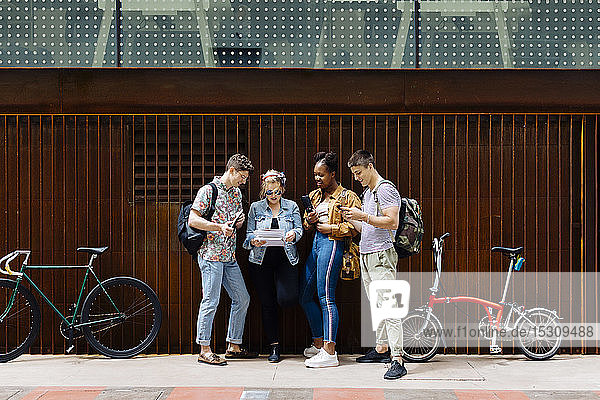 Students standing in the street  holding smartphones  reading papers