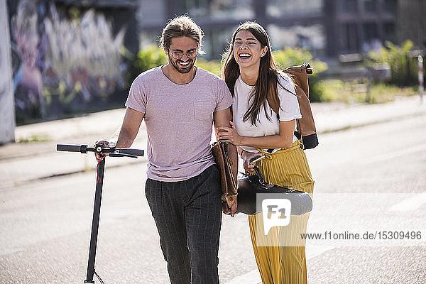 Glückliches junges Paar mit Elektroroller auf der Straße