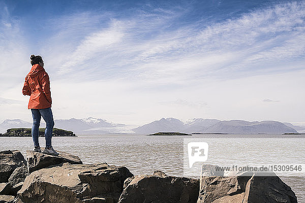Young woman standig boulders  looking at the sea  South East Iceland