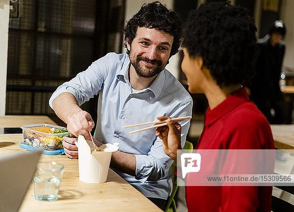 Kollegen im Büro machen Mittagspause und teilen chinesisches Essen zum Mitnehmen