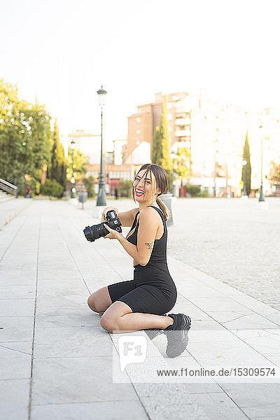 Porträt einer glücklichen jungen Frau mit Kamera auf einer Treppe kniend