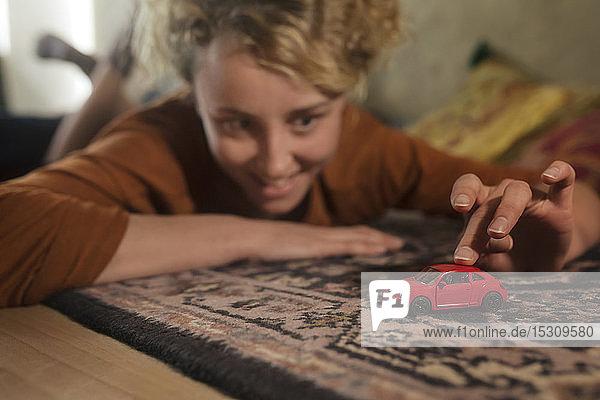 Junge Frau liegt auf Teppich und spielt mit rotem Spielzeugauto