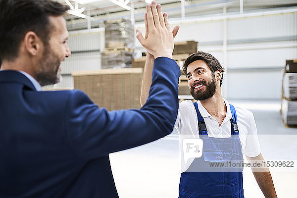 Happy businessman and worker high fiving in a factory