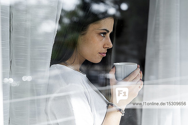 Young woman with cup of coffee behind windowpane