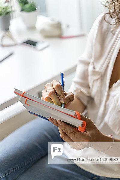Nahaufnahme einer Frau  die zu Hause am Schreibtisch Notizen macht