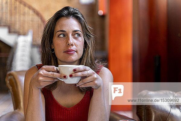 Porträt einer jungen Frau mit Tasse Kaffee