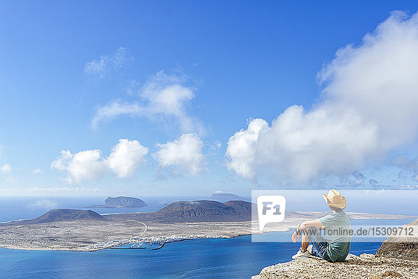 Man on viewpoint looking to La Gracioas island from Lanzarote  Canary Islands  Spain
