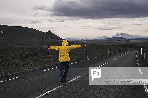 Mann balanciert auf der Mittellinie einer leeren Straße  Island