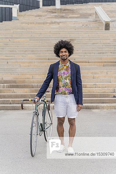 Porträt eines stilvollen Mannes mit Fahrrad an einer Treppe stehend
