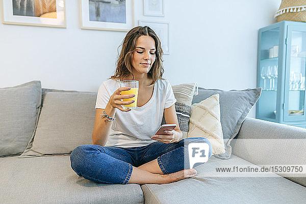 Junge Frau sitzt mit Saft auf dem Sofa und telefoniert mit ihrem Handy