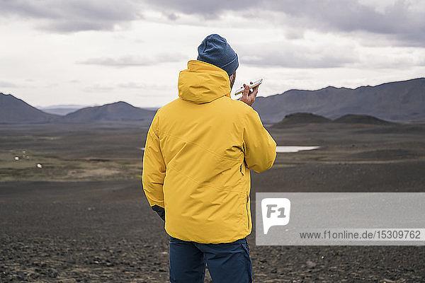 Reifer Mann spricht auf seinem Smartphone im isländischen Hochland