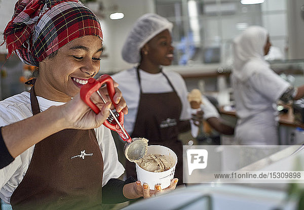 Young woman working in ice cream parlour  filling cup with icecream