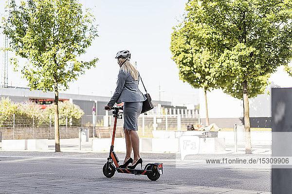 Geschäftsfrau mit hochhackigen Schuhen fährt Elektroroller auf der Straße