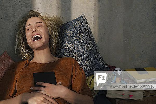 Porträt einer lachenden  auf dem Bett liegenden jungen Frau mit E-Book-Reader
