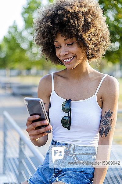 Porträt einer tätowierten jungen Frau im Sommer beim Blick auf ein Smartphone