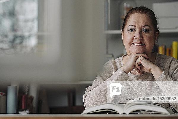 Porträt einer lächelnden älteren Frau mit Buch zu Hause