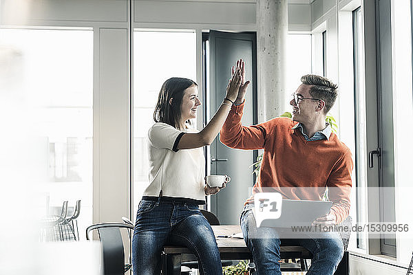 Happy casual businessman and woman high fiving in office