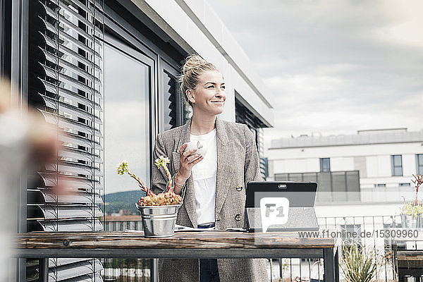 Businesswoman with coffee cup and tablet on roof terrace