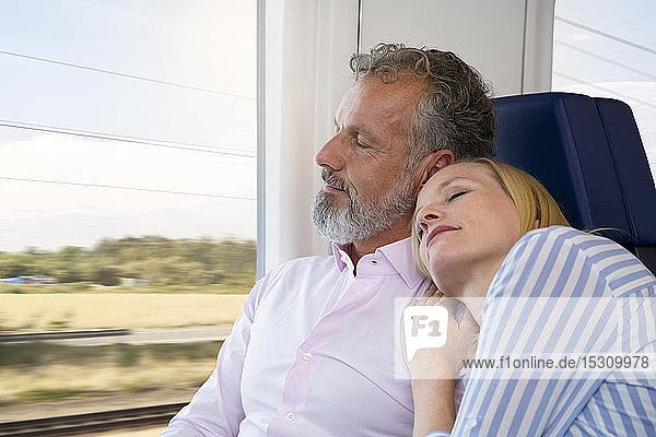 Paar reist mit dem Zug  die Frau stützt sich auf die Schulter des Mannes