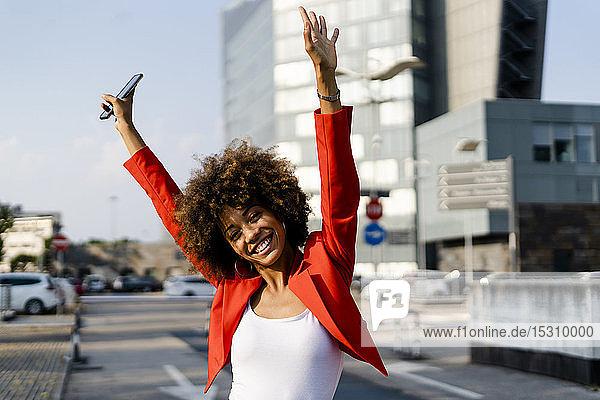 Porträt einer glücklichen jungen Frau mit Smartphone in modischer roter Anzugsjacke