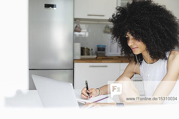 Junge Frau benutzt ihren Laptop zu Hause