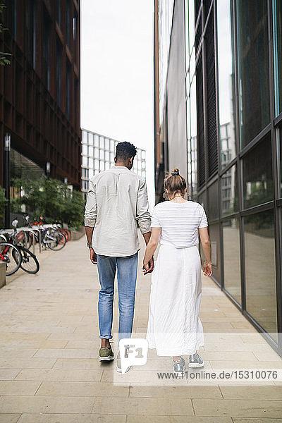 Rückenansicht eines jungen Paares  das Hand in Hand auf dem Bürgersteig geht