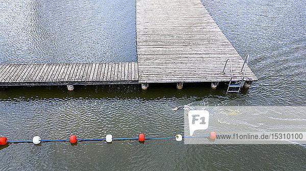 Luftaufnahme eines Triathleten  der in einem See krabbelt