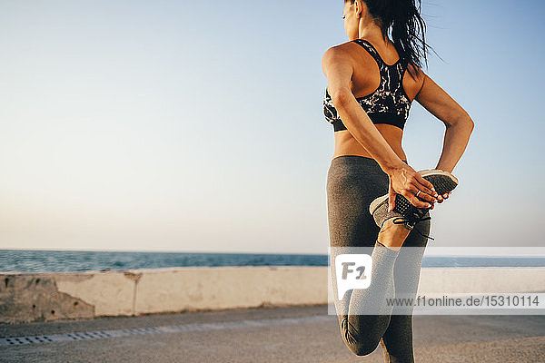 Junge Sportlerin streckt ihr Bein auf einem Steg