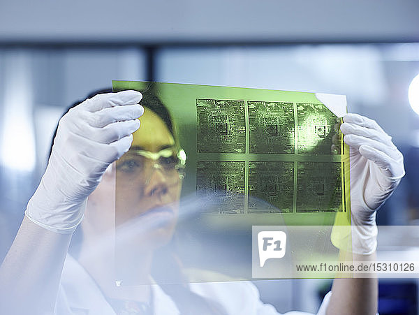 Female technician controlling foil printing with circuitry