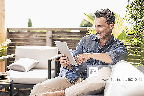 Mature man sitting on terrace  using digital tablet