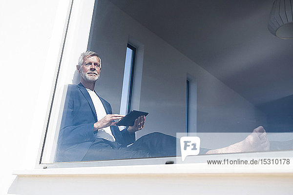 Senior businessman sitting at panorama window using tablet