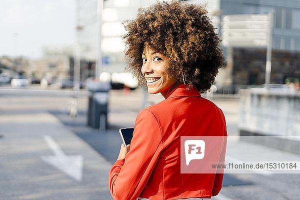 Porträt einer lächelnden jungen Frau mit Smartphone in modischer roter Anzugsjacke