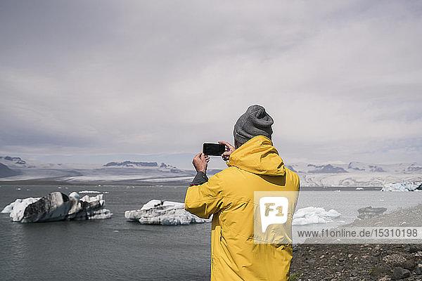 Erwachsener Mann fotografiert den Vatnajokull-Gletscher mit einem Fernglas  Island