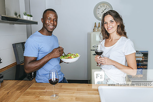 Couple eating salad and drinking wine in the kitchen