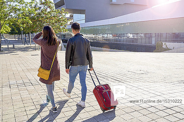 Tourist couple walking with a wheel suitcase  Barcelona  Spain