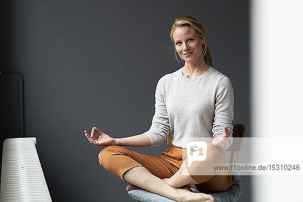 Junge Frau  die im Büro auf einem Stuhl sitzt und Yoga praktiziert