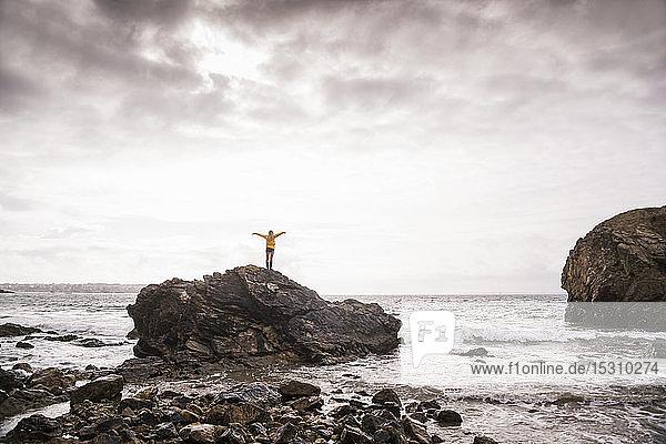 Rückansicht einer Frau mit erhobenen Armen  am Felsstrand stehend