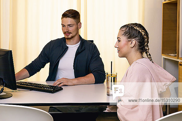 Young woman talking to employee at desk in a gym